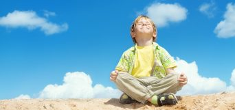Happy child sitting in lotus position over bllue sky on the top. Happiness and freedom concept.